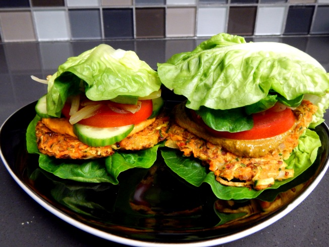 Zucchini cakes with lettuce leaves instead of a bun, making it handheld.